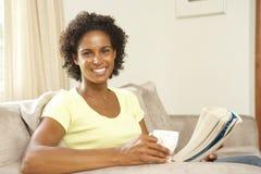 Frau, die sich zu Hause auf Sofa entspannt lizenzfreies stockbild