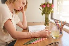 Frau, die sich zu Hause durch Malbuch entspannt Lizenzfreie Stockbilder