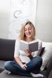Frau, die sich zu Hause entspannt, ein Buch lesend Lizenzfreie Stockfotos
