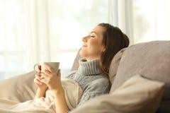 Frau, die sich zu Hause entspannt, eine Kaffeetasse halten lizenzfreie stockfotografie