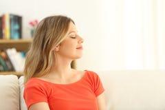 Frau, die sich zu Hause mit geschlossenen Augen entspannt stockfotografie