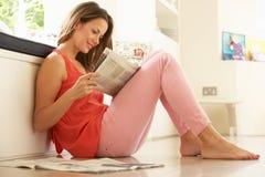 Frau, die sich zu Hause mit Zeitung entspannt Lizenzfreie Stockfotos