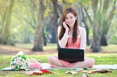 Frau, die an sitzen und Unterhaltungshandy Lizenzfreie Stockfotos