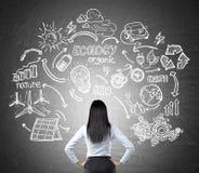 Frau, die Skizzen der erneuerbaren Energiequellen auf Tafel betrachtet Stockfotos