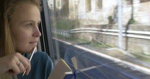 Frau, die Skizzen während der Zugfahrt macht stock footage