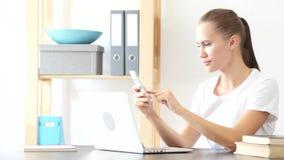 Frau, die Smartphone-Anwendungen bei der Arbeit im Büro verwendet lizenzfreies stockfoto