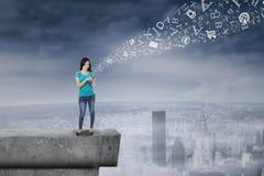 Frau, die Smartphone auf Dachspitze verwendet Lizenzfreie Stockfotografie