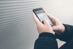 Frau, die Smartphone auf der Straße gegenüberstellt die Wand verwendet Lizenzfreie Stockfotos
