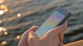 Frau, die Smartphone auf Plattform des Kreuzschiffs bei Sonnenuntergang verwendet stock video