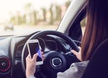 Frau, die Smartphone auf Straße fährt und verwendet Stockfotos