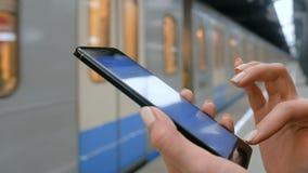 Frau, die Smartphone auf U-Bahnplattform verwendet stock video footage
