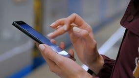 Frau, die Smartphone auf U-Bahnplattform verwendet stock footage