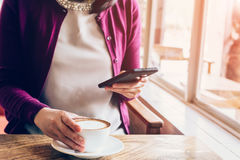 Frau, die Smartphone in der Kaffeestube verwendet Stockfoto