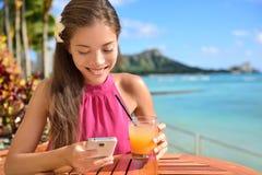 Frau, die Smartphone an der Strandbar etwas trinkend verwendet Stockfotos