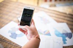 Frau, die Smartphone Diagramm auf Schirm zeigt Stockfotos