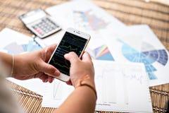 Frau, die Smartphone Diagramm auf Schirm zeigt Lizenzfreie Stockfotografie