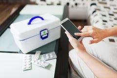 Frau, die Smartphone für kaufende Pillen on-line-Apotheke verwendet Lizenzfreie Stockfotos