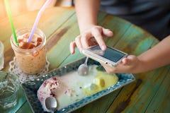 Frau, die Smartphone im Café verwendet Stockfotografie