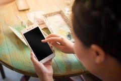 Frau, die Smartphone im Café verwendet Lizenzfreie Stockfotografie