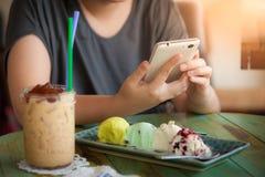 Frau, die Smartphone im Café verwendet Stockfotos