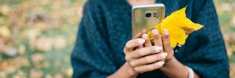 Frau, die Smartphone im Herbst verwendet stockfotografie