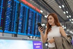 Frau, die Smartphone mit Fluginformationsbrett am Flughafen verwendet stockfotos