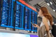 Frau, die Smartphone mit Fluginformationsbrett am Flughafen verwendet stockfotografie