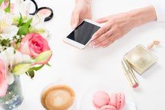 Frau, die Smartphone mit leerem Bildschirm nahe Blumen verwendet Kosmetik und macarons stockbilder
