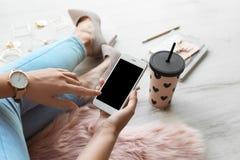 Frau, die Smartphone mit leerem Bildschirm verwendet lizenzfreies stockbild