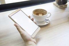 Frau, die Smartphone, Nahaufnahme, Kaffee verwendet und Buch auf t plant Lizenzfreies Stockfoto