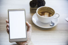 Frau, die Smartphone, Nahaufnahme, Kaffeetasse auf dem Hintergrund verwendet Lizenzfreie Stockbilder