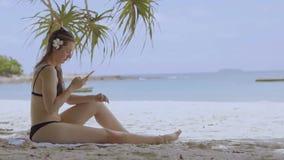 Frau, die Smartphone am Strandtrinken verwendet Schließen Sie oben von der Frauenholding stock video