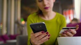 Frau, die Smartphone und Kreditkarte für Online-Zahlung im Caféabschluß aufbraucht stock video footage
