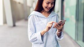 Frau, die Smartphone, während der Freizeit verwendet Das Konzept der Anwendung des Telefons ist im Alltagsleben wesentlich lizenzfreies stockfoto