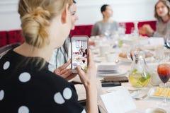 Frau, die Smartphoneschüsse auf Bankett nimmt Stockbilder