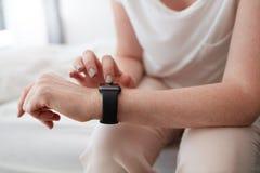 Frau, die smartwatch verwendet, um Zeit zu überprüfen Lizenzfreie Stockbilder