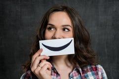 Frau, die Smiley Emoticon hält Lizenzfreies Stockbild