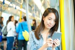 Frau, die sms auf Mobiltelefon im Zug sendet Lizenzfreies Stockfoto