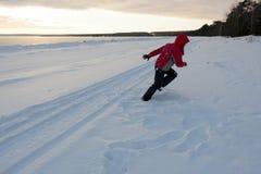 Frau, die an Snowy-Strand läuft Lizenzfreie Stockbilder