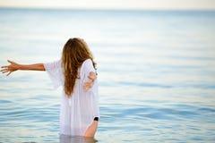 Frau, die Sommerfreiheit mit den offenen Armen am Strand genießt Stockfotografie