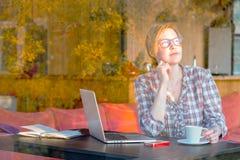 Frau, die Sonnenaufgang-Ansicht in gemütlichen Hauptinnenraum genießt Lizenzfreie Stockfotos