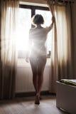 Frau, die Sonnenaufgang durch Fenster betrachtet Lizenzfreies Stockfoto