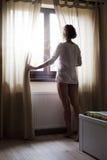 Frau, die Sonnenaufgang durch Fenster betrachtet Stockbilder