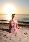 Frau, die am Sonnenaufgang meditiert Stockfotos