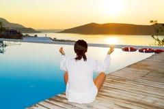 Frau, die am Sonnenaufgang meditiert Stockfotografie