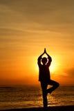 Frau, die am Sonnenaufgang meditiert Lizenzfreies Stockbild