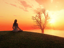 Frau, die am Sonnenaufgang meditiert Lizenzfreie Stockfotos