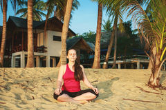 Frau, die am Sonnenaufgang meditiert Stockbild
