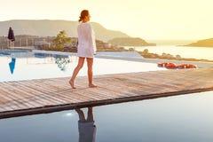 Frau, die am Sonnenaufgang nahe Swimmingpool geht Stockfoto