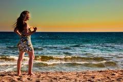 Frau, die Sonnenaufgang am Strand genießt Lizenzfreie Stockfotografie